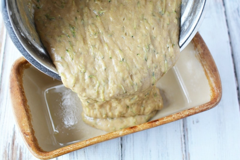 Pouring zucchini mixture into loaf pan for zucchini bread