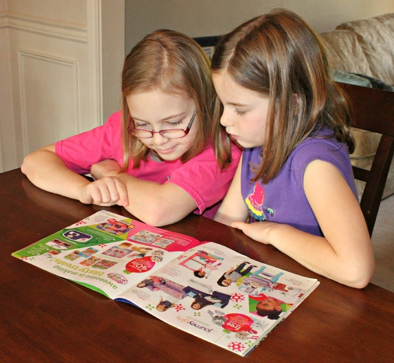 Kids Reading the Great Big Toys R Us Book of Awesome toy catalog