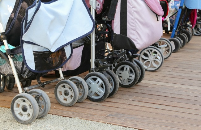 many wheels of strollers for toddlers parked on the wooden parquet floor