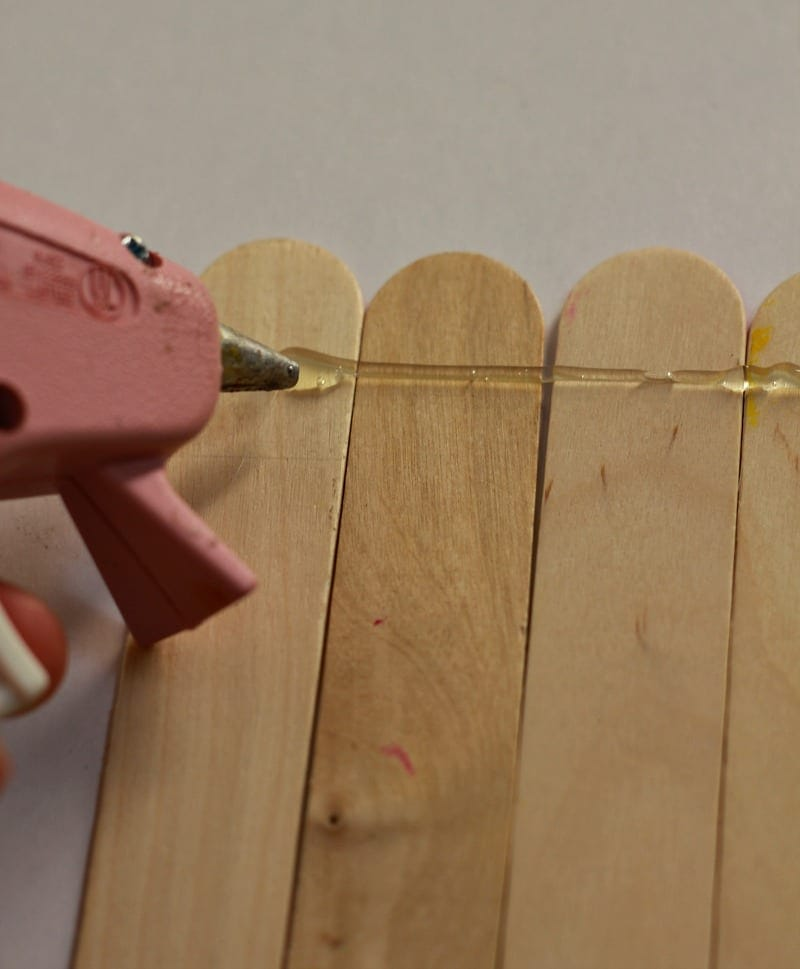 Hot glue gun with popsicle sticks to make DIY Pencil Frame