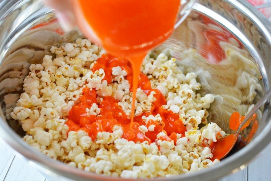 Pouring mixture onto popcorn for candied popcorn